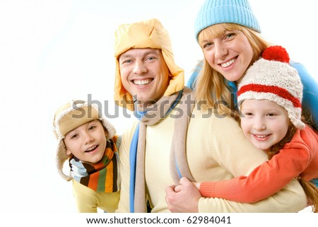 Two children and wife in winter clothes embracing a happy man on white background - stock photo