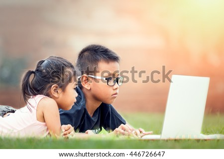 Two children are playing notebook at park  - stock photo
