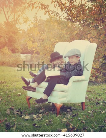Two children are sitting in the park reading a book story and laughing in a white chair for an education or peace concept - stock photo