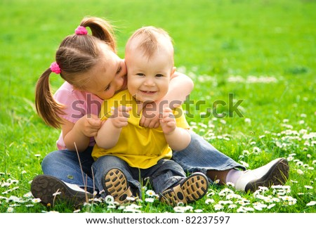 Two children are sitting on green meadow and smile - stock photo