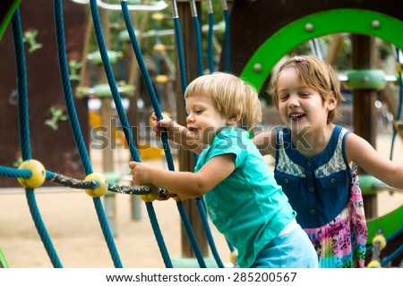 Two children at action-oriented playground in park - stock photo