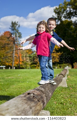 Two children balancing on a log in  the fall - stock photo
