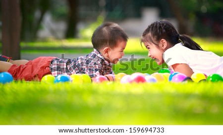 Two children, big syster and her young brother are laying on green grass and smile - stock photo
