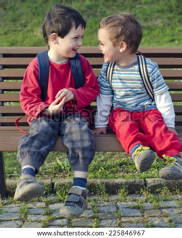 Two children boys, friends or brothers sitting on a bench, talking and laughing. - stock photo