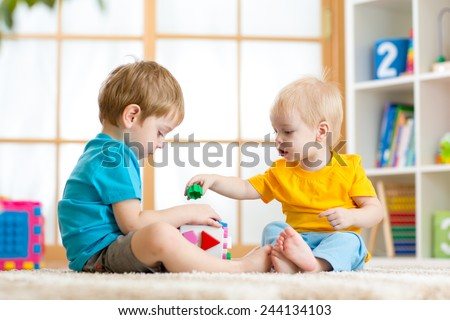 two children boys play together educational toys in playroom - stock photo