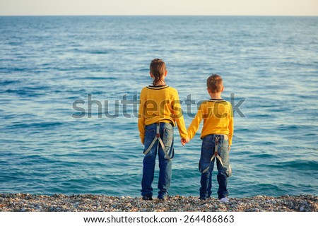 Two children, brothers, boys in yellow pullovers, standing on a beautiful pebble beach holding hands, view from the back - stock photo