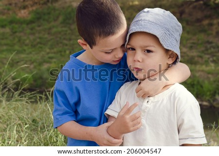 Two children brothers playing and hugging  in nature. - stock photo