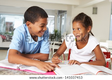 Two Children Doing Homework Together In Kitchen - stock photo
