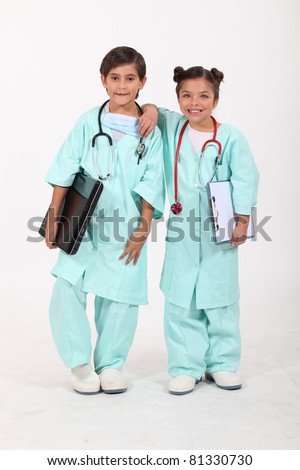 Two children dressed as doctors - stock photo