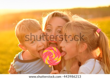 Two children eat lollipop with mother  - stock photo