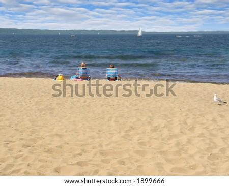 Two children enjoy their beachfront view of the lake - stock photo