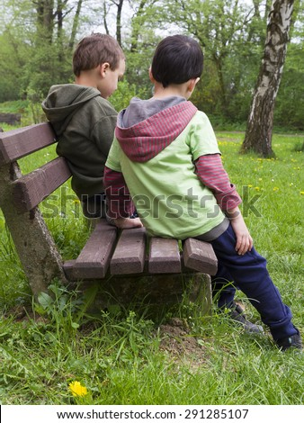 Two children friends or brothers on a bench in spring park, back view. - stock photo