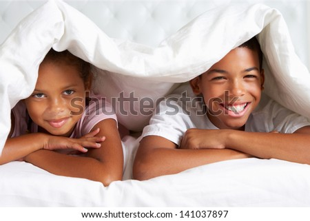 Two Children Hiding Under Duvet In Bed - stock photo
