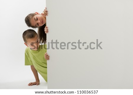 Two children holding a blank sign and looking at it; you can add your own text - stock photo