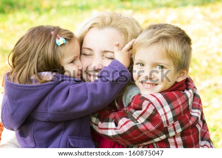 Two children hugging mother, focus on boy - stock photo