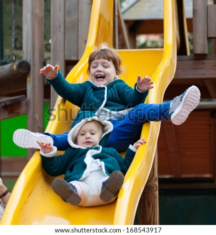 two children  in jacket on slide at playground area - stock photo
