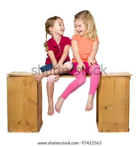 Two children laughing sitting on a bench. Isolated on a white background - stock photo