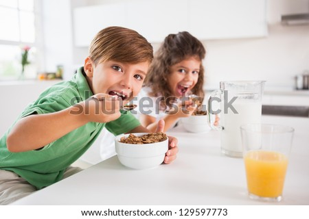 Two children looking at camera while eating cereal in kitchen - stock photo