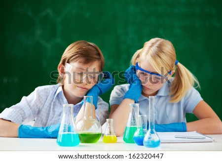 Two children looking at tubes with chemical liquids - stock photo