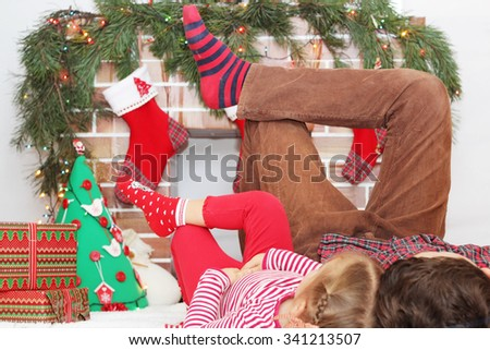 Two children lying on their backs with their legs lifted up near Christmas decorated fireplace, winter holiday family concept - stock photo