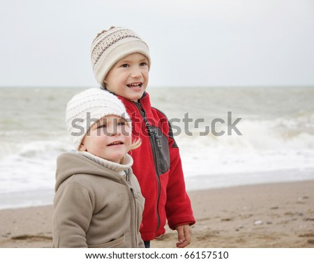 two children on winter sea background - stock photo