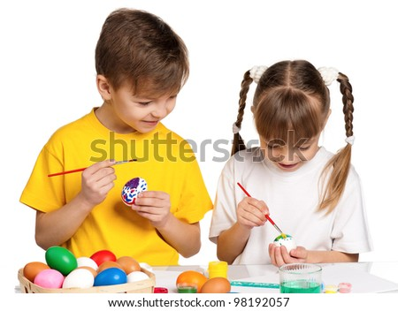 Two children painting Easter eggs isolated on white background - stock photo