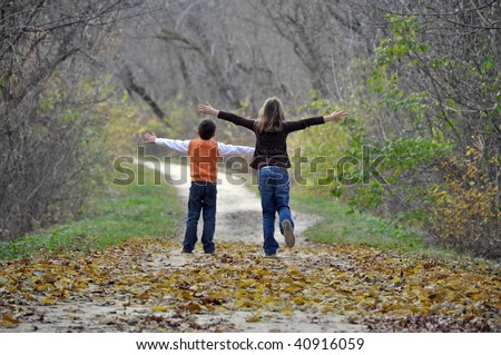 two children playfully run down a tree lined path on a beautiful autumn day - stock photo