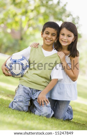 Two children playing football in park looking to camera - stock photo