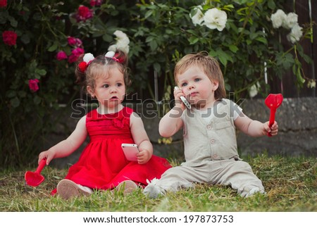 Two children playing in the rose graden - stock photo