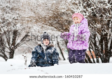 two children playing in the snow - stock photo