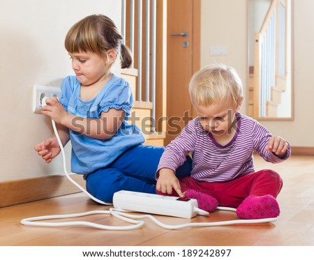 Two children  playing with electrical extension and outlet on floor at home - stock photo