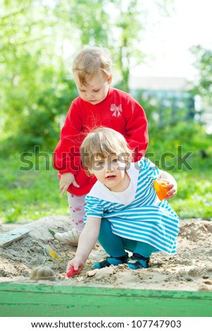 two children playing with sand in sandbox - stock photo