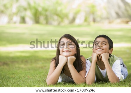 Two children relaxing in park together - stock photo