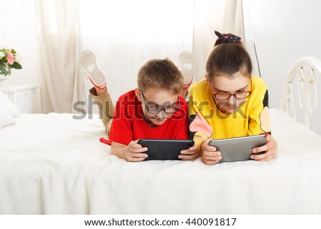 Two children, siblings on parents' bed at morning with tablets. Brother and sister play computer games. Siblings and gadgets. Children in glasses. Girl and boy play at device - stock photo