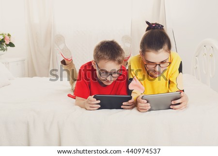 Two children, siblings on parents' bed at morning with tablets. Brother and sister play computer games at their gadgets. Girl and boy in glasses look at devices - stock photo