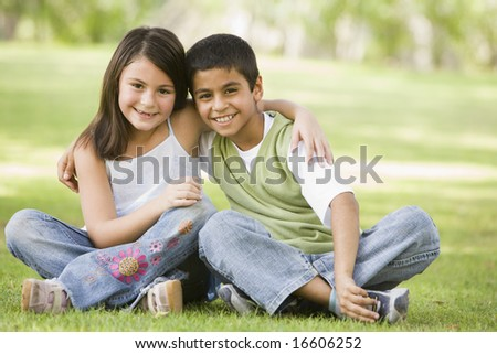 Two children sitting in park together - stock photo
