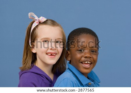Two children smiling together - an African American boy and a Caucasian girl with a ribbon in her hair. - stock photo