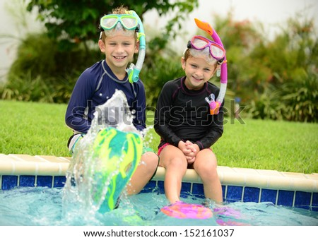 two children splashing water with swimming fins in pool - stock photo