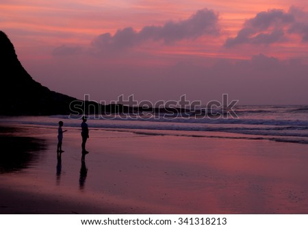 Two children standing on the beach, overlooking the distant as if thinking. paper cut silhouette 	  - stock photo