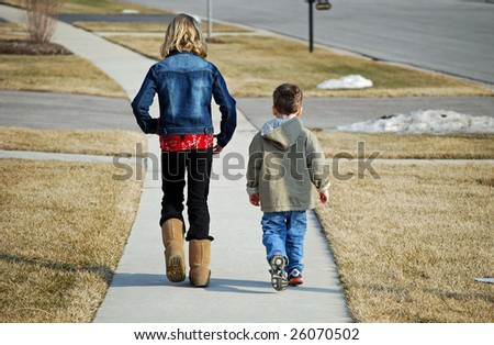 two children take a walk on one of the first warm days of early spring - stock photo