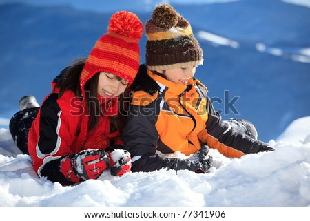 Two children the snow ski wearing winter coats and knit hats in winter. - stock photo