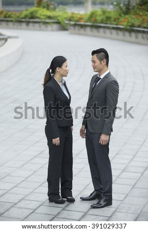Two Chinese Business colleagues standing outside office & talking to each other. - stock photo