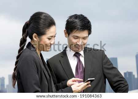 Two Chinese business people standing looking at smart mobile phone. Urban cityskyline in background. - stock photo