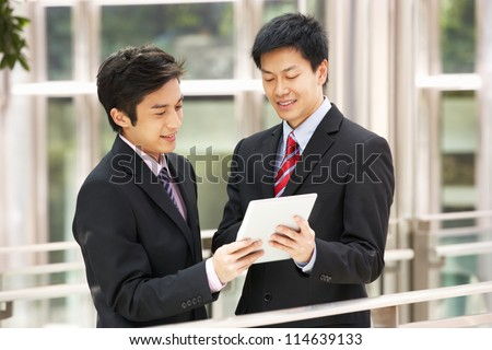 Two Chinese Businessmen Using Tablet Computer Outside Office - stock photo
