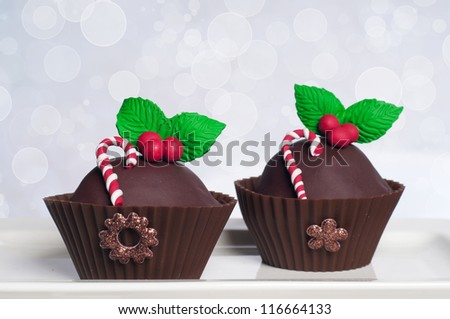 Two chocolate Christmas cupcakes with holly and candy canes on bokeh background - stock photo