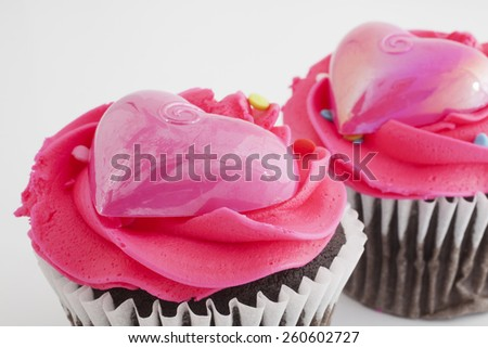 Two chocolate cupcakes with pink frosting and plastic hearts - stock photo