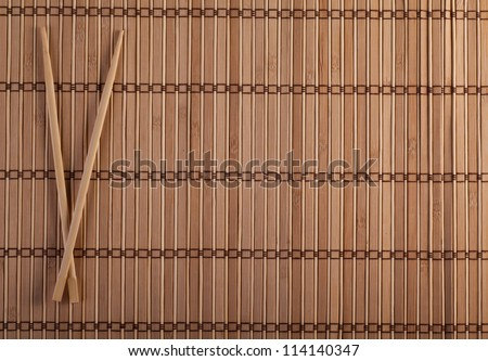 Two chopsticks on sushi mat background for menu - stock photo