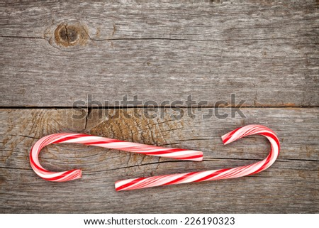 Two christmas candy cane over wooden background with copy space - stock photo