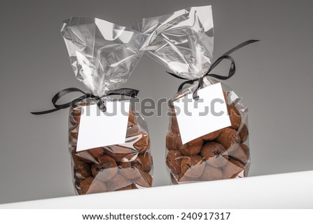 Two Christmas gifts with elegant black ribbons of chocolate truffles. Blank label that you can add your own trademark or your own message. Fun composition. Shooting on grey background in studio. - stock photo