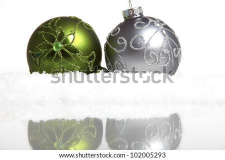 Two Christmas tree balls in the snow mirrored on white background - stock photo